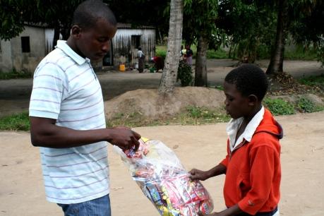 Gilton, uno de los educadores, repartiendo un aperitivo entre los niños del centro / Moncho Torres